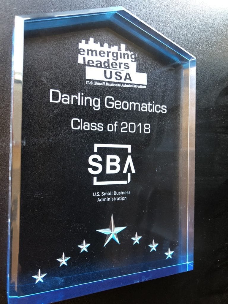 "crystal trophy on a black background, the text on the plaque says ""emerging leaders USA, Darling Geomatics, Class of 2018, US Small Business Administration"